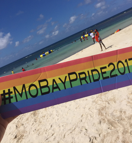 Montego Bay Pride 2017 hashtag (#MoBayPride2017) on a sign held in hand with the beach in Montego Bay, Jamaica, in the background.