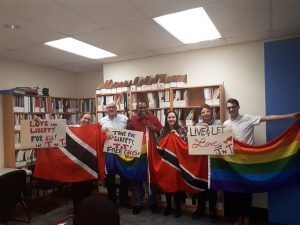 Six individuals standing in a row, holding the flags of Trinidad and Tobago and the rainbow flag.